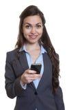 Femme d'affaires avec le long message brun d'écriture de cheveux avec le téléphone Photos stock