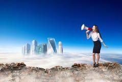 Femme d'affaires avec le mégaphone au bord de la gamme de montagne image stock