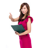 Femme d'affaires avec le presse-papiers et le pouce  Photographie stock libre de droits