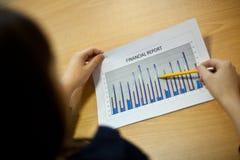 Femme d'affaires avec le rapport financier au bureau (foyer sur le rapport) Photos stock