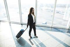 Femme d'affaires avec le sac de laggage marchant dans l'aéroport Photographie stock libre de droits