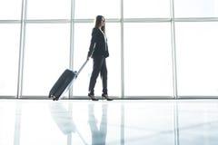 Femme d'affaires avec le sac de laggage marchant dans l'aéroport Image libre de droits