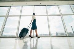 Femme d'affaires avec le sac de laggage marchant dans l'aéroport pour déclencher Photo libre de droits