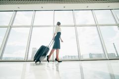 Femme d'affaires avec le sac de laggage marchant dans l'aéroport pour déclencher Image stock