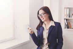 Femme d'affaires avec le téléphone portable à la fenêtre de bureau Photographie stock libre de droits