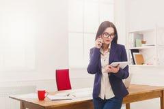 Femme d'affaires avec le téléphone portable et le comprimé Photos libres de droits