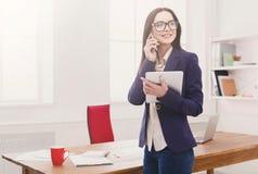 Femme d'affaires avec le téléphone portable et le comprimé Photo stock