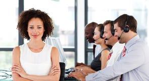 Femme d'affaires avec les bras pliés à un centre d'attention téléphonique Photo libre de droits