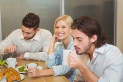 Femme d'affaires avec les collègues masculins ayant les casse-croûte et le café dans la cantine Image libre de droits