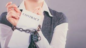 Femme d'affaires avec les mains enchaînées tenant le contrat Photo stock