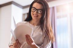 Femme d'affaires avec plaisir intelligente regardant par les documents Image stock