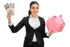 Femme d'affaires avec plaisir tenant des paquets et la tirelire d'argent Photo stock