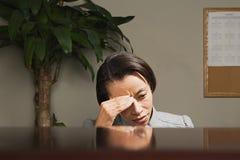 Femme d'affaires avec sa tête dans des ses mains Photo libre de droits