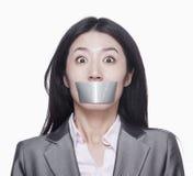 Femme d'affaires avec son caver de bouche avec le ruban adhésif photos stock