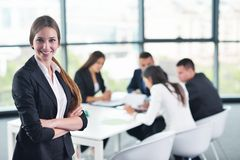 Femme d'affaires avec son personnel à l'arrière-plan au bureau photographie stock