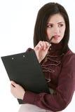 Femme d'affaires avec un dossier touchant ses lèvres avec un stylo Photographie stock libre de droits