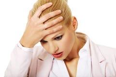 Femme d'affaires avec un mal de tête énorme tenant la tête Photographie stock libre de droits