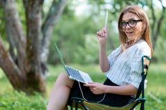 Femme d'affaires avec un ordinateur portable se reposant en parc sur un pliage ch photo stock
