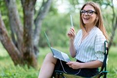 Femme d'affaires avec un ordinateur portable se reposant en parc sur un pliage ch images libres de droits