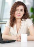 Femme d'affaires avec un ordinateur portatif et une tasse Image stock