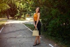 Femme d'affaires avec un sac à la mode dans des ses mains posant sur la nature en parc photographie stock libre de droits