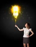 Femme d'affaires avec une ampoule qui respecte l'environnement Images stock