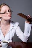 Femme d'affaires avec une tasse de café et d'une barre de chocolat Photographie stock libre de droits