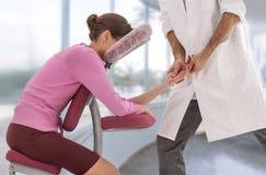 Femme d'affaires ayant l'anti massage de tresse dans le bureau médical avec grand, fenêtres, fond, photos stock