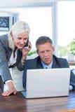 Femme d'affaires ayant l'appel téléphonique et regardant l'ordinateur portable avec ses collègues Photo libre de droits