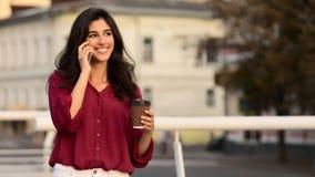 Femme d'affaires ayant la coupure, café potable et parlant au téléphone images stock