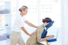 Femme d'affaires ayant le massage arrière tout en à l'aide de son ordinateur portable image stock
