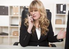 Femme d'affaires ayant un argument au-dessus du téléphone photo stock