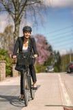 Femme d'affaires Biking à la rue avec le casque photo libre de droits