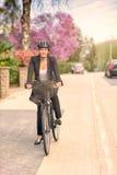 Femme d'affaires Biking à la rue avec le casque images stock