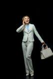Femme d'affaires blonde à l'aide du smartphone dans le costume blanc Image libre de droits