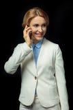 Femme d'affaires blonde à l'aide du smartphone dans le costume blanc Photographie stock