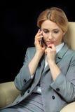Femme d'affaires blonde à l'aide du smartphone se reposant sur le fauteuil Image stock