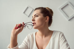 Femme d'affaires blonde attirante songeuse avec des lunettes dans le bureau moderne Image stock