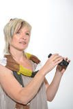 Femme d'affaires blonde avec l'écharpe regardant avec des jumelles Photographie stock libre de droits