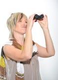 Femme d'affaires blonde avec l'écharpe regardant avec des jumelles Photographie stock