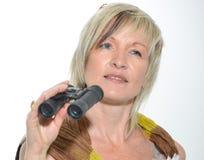 Femme d'affaires blonde avec l'écharpe regardant avec des jumelles Photos stock