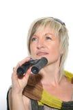 Femme d'affaires blonde avec l'écharpe regardant avec des jumelles Images stock