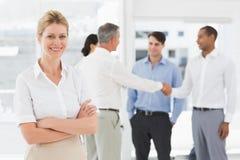 Femme d'affaires blonde avec l'équipe derrière elle souriant à l'appareil-photo Photographie stock libre de droits