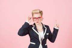 Femme d'affaires blonde avec les verres rouges se dirigeant par le doigt sur le fond rose image stock
