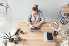 Femme d'affaires blonde dactylographiant sur l'ordinateur portable dans le bureau moderne Photo libre de droits