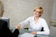 Femme d'affaires blonde dans la poignée de main en verre photos stock