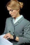 Femme d'affaires blonde dans le contrat de lecture de tenue de soirée Image libre de droits