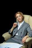Femme d'affaires blonde dans le costume gris se reposant sur le fauteuil Images stock