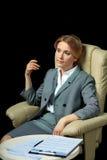 Femme d'affaires blonde dans le costume gris se reposant sur le fauteuil Photos libres de droits
