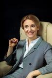 Femme d'affaires blonde dans le sourire gris de costume Photo libre de droits